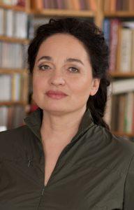 Portrait von Barbara Stoll vor einem Bücherregal