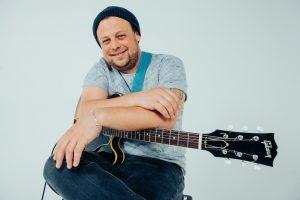 Portrait von Christoph Neuhaus mit E-Gitarre