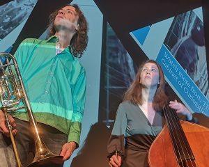 Posaunist und Kontrabassistin schauen vor einer Videoprojektion in die Ferne