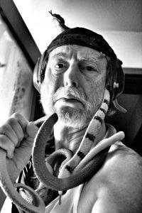 Portrait von Claus Staudt, der Schlangen um seinen Hals trägt