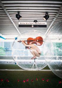 ein leicht bekleideter Mensch mit einem Cello auf dem Rücken in einer durchsichtigen Kugel