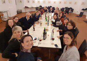 Etwa 20 Damen und Herren sitzen um einen Tisch und lächeln in die Kamera
