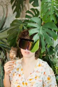 junge Frau mit Locken, Skibrille und Minieule auf der Hand vor einer Monstera deliciosa