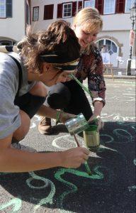 zwei junge Menschen bemalen die Straße mit leuchtend grünen Linien