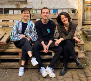 die drei jungen Musiker:innen von reizÜBERFLUTung sitzen auf einem Palettenmöbel