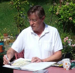 Albrecht Weckmann zeichnend an einem Tisch im Freien sitzend