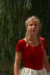 Eine junge Frau mit blonden Zöpfen und rotem Shirt
