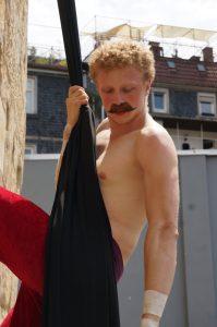 Ein Artist mit angeklebtem Schnäuzer turnt an einem langen schwarzen Stofftuch