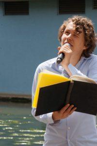 Philipp Falser hält ein Buch mit schwarzem Umschlag und gelben Seiten und spricht in ein Mikrofon